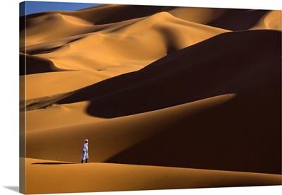 Berber Man Walking In The Erg Chebbi Sand Sea, Sahara Desert, Morocco