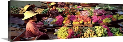 Market traders in boats laden with fruit and flowers, Bangkok, Thailand
