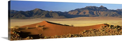Panoramic view over orange sand dunes towards mountains, Namibia, Africa