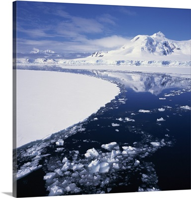 Reflections in icy sea of snow covered mountain, Antarctica