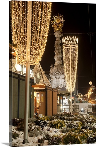 snow covered flowers christmas decorations and baroque trinity column austria