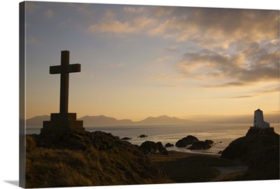 Stone Cross and old lighthouse in silhouette at sunset, Anglesey, North Wales, UK