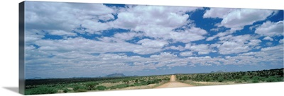Straight gravel road cutting across grassy plain near Windhoek, Namibia