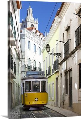 Tram along Rua das Escolas Gerais with tower of Sao Vicente de Fora, Lisbon, Portugal