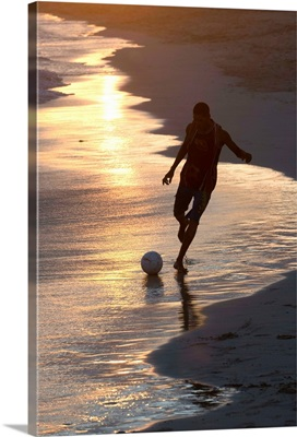Young man playing football at sandbeach in twilight, Sal, Cape Verde, Africa