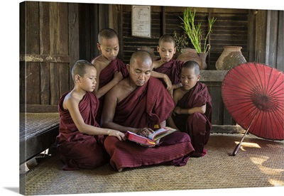 Burmese monkmaster and young monks in their monastery