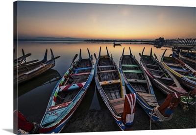 Colorful longtail boats at sunrise at the Ubein Bridge in Mandalay, Burma