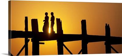 Couple walking across the Ubein Bridge in Burma at sunset