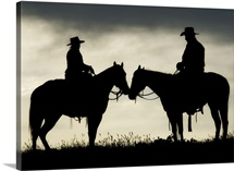 Cowboy and cowgirl on horseback by lake at sunset