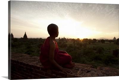 Monk boy atop temple in at sunset, Pagan, Burma