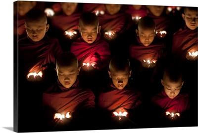Monk boys praying by candle light in their monastery, Yangon, Burma