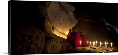 Monk boys praying by giant Buddha in Bagan, Burma
