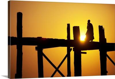 Monk walking across the Ubein Bridge in Burma at sunset