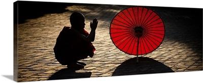 Monk with parasol praying in Bagan, Burma