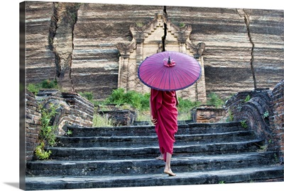 Monk with parasol walking up the steps to Mingun Monastery in Burma