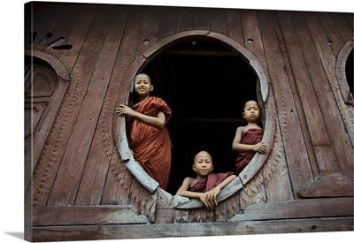 Monks in window of their monastery, Inle Lake, Burma