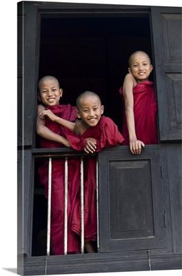 monks in window of their monastery, Mandalay, Burma