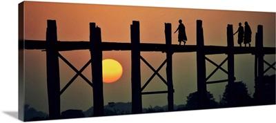 Monks walking across the Ubein Bridge in Burma at sunset