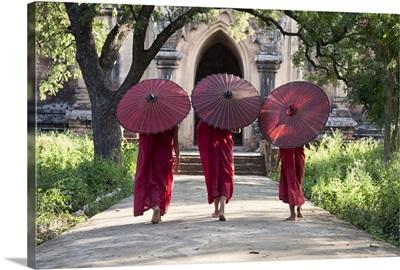 monks walking with parasols in monastery, Bagan, Burma