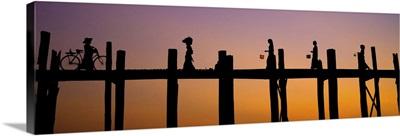 People crossing the Ubein Bridge in Mandalay, Burma, at sunset