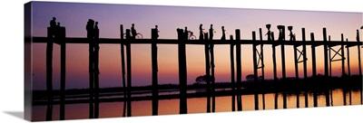 People walking across the UBein bridge at sunset in Mandalay
