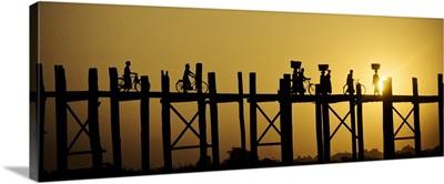 People walking across the UBein bridge at sunset in Mandalay, Burma