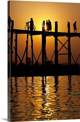 People walking across the Ubein Bridge in Burma at sunset