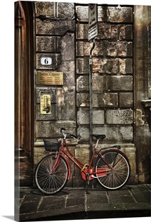 Red bicycle by stone wall, Florence, Italy