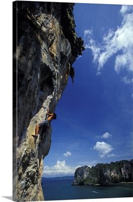 Rock climber above the ocean in Railay Beach, Krabi, Thailand