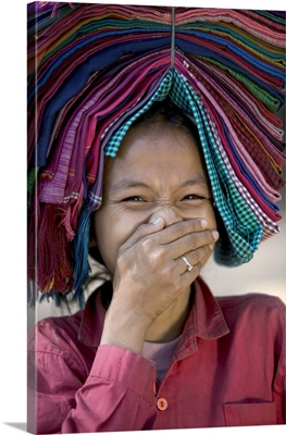 Smiling girl carries goods for sale on her head, Cambodia, South East Asia