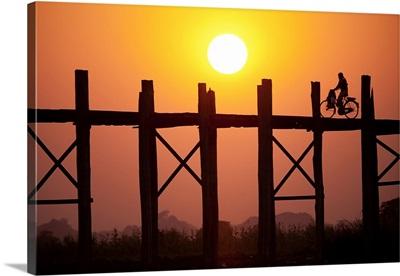 Woman on her bike across the Ubein Bridge in Burma at sunset