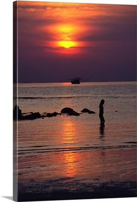 Woman walking on beach at sunset, Koh Samui, Thailand