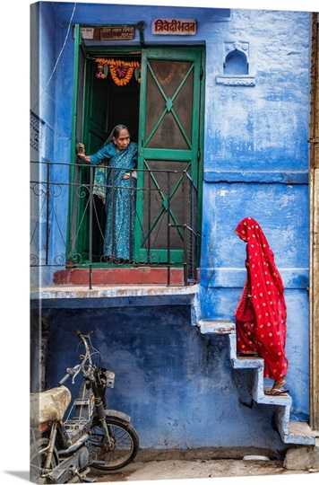 Woman with red Sari walking up steps in the blue city of Jodphur