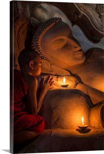 Young Burmese monk praying by candlelight by reclining Buddha