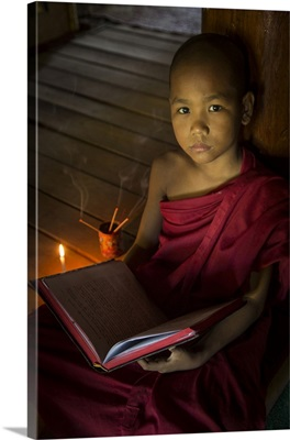 Young Burmese monk reading by candlelight