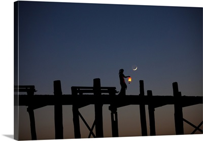 Young girl with lantern crossing the Ubein Bridge at night, Mandalay, Burma