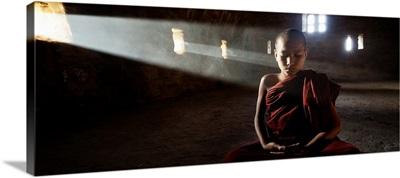 Young monk praying in his monastery, Bagan, Burma