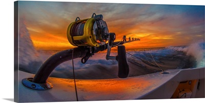 The reel of a big game fishing rod on the side of a boat, with the setting sun behind