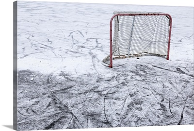 An ice hockey net on an outdoor pond rink