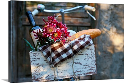 Bicycle with picnic snack in wooden box on old wooden surface