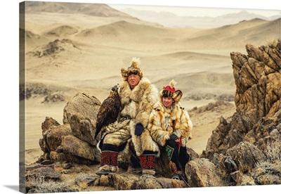 Kazakh Eagle Hunter In Desert Mountains, Golden Eagle Festival, Olgei, Mongolia