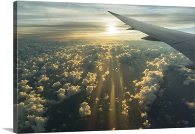 View From Airplane Side Window Of Sunset Sky And Sunlit Clouds