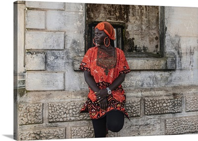 Woman Stands By Old Building With Traditional Orange African Dress, Takoradi, Ghana