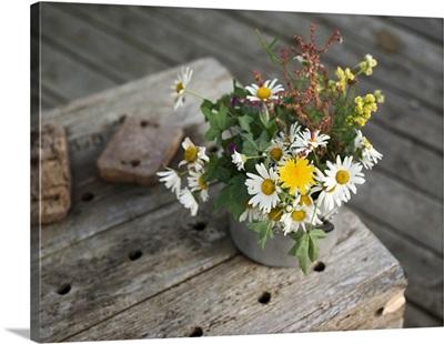 A bunch of meadow flowers in a metal pot on an old wooden shelf