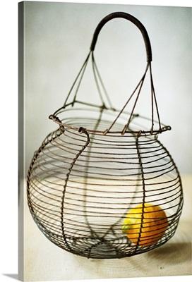 A lemon in a wire basket