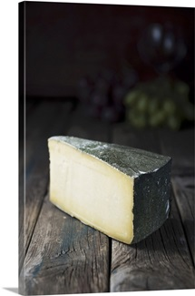 A slice of hard cheese on a wooden table