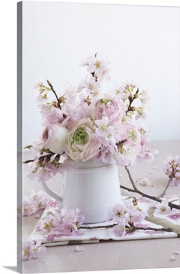 A spring bouquet of ranunculus flowers and ornamental cherry blossom in a tankard vase