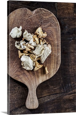 Assorted fresh mushrooms on a wooden chopping board