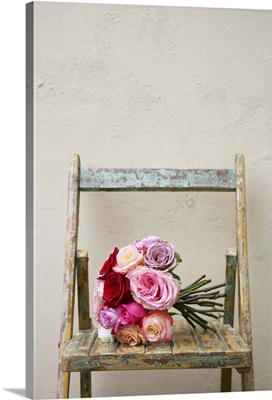 Bouquet of roses of different colours on weathered wooden chair