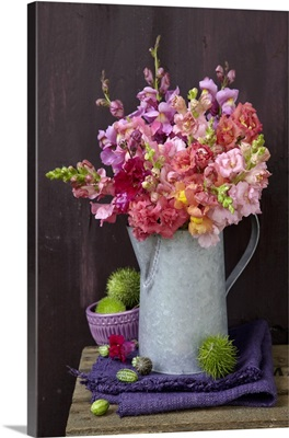 Bouquet of snapdragons in zinc jug and spiky sweet chestnuts on folded linen cloth